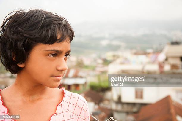 Indian descent, pre-teenage girl portrait. Village in background.