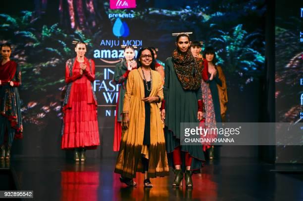 Indian designer Anju Modi greets during the Amazon India Fashion Week Autumn Winter 2018 in New Delhi on March 16 2018 / AFP PHOTO / CHANDAN KHANNA