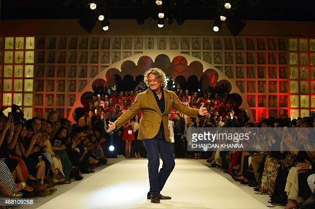 Indian designer Rohit Bal dances as other designers watch during the final presentation of AutumnWinter 2015 collections at the India Fashion Week in...