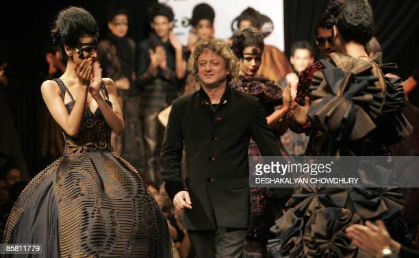 Indian designer Rohit Bal walks past models wearing his creations on April 5 2009 during the grand finale of the Kolkata Fashion Week in Kolkata The...