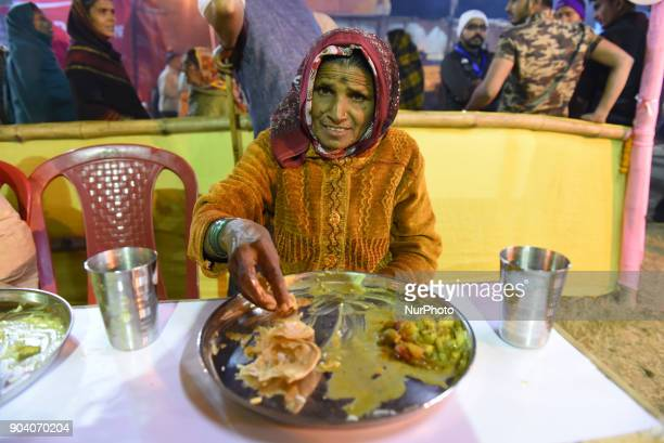 Indian devotee blows conch shell prior to intake her evening meal as others stand in a queue outside at a transit camp on the way to Gangasagar on...