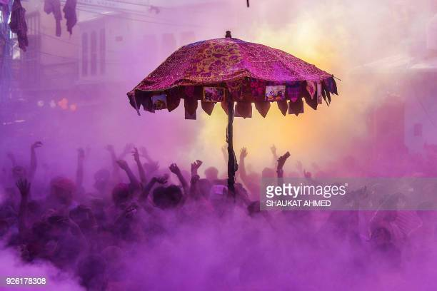 TOPSHOT Indian devotees and foreign tourists take part in the 'kapda phaar' or cloth tearing during Holi festival celebrations in Pushkar in the...