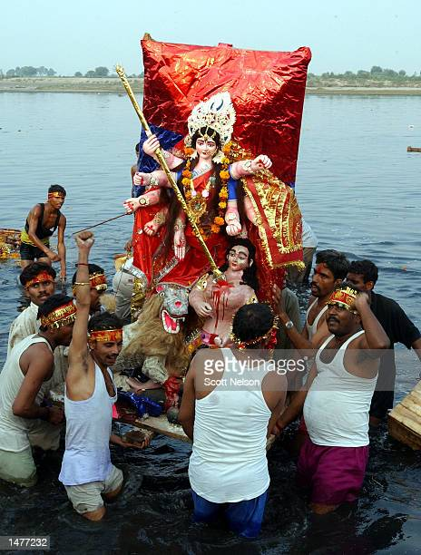 Indian devotees carry a statue of the Hindu goddess Durga into the Yamuna river during a celebration marking the end of the Durga Puja festival...