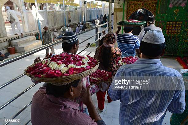 Indian devotees carry flowers and other offerings as they arrive at the Ajmer Sharif shrine in Ajmer on March 9 2013 Pakistan's Prime Minister Raja...
