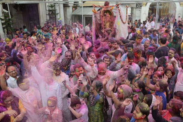 Indian devotees covered with coloured powder carry an idol of Lord Krishna during Holi celebrations at a temple in Amritsar on March 1 2018 Holi the..