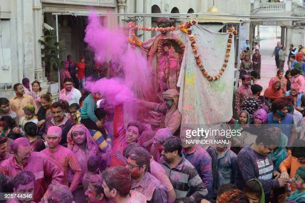 Indian devotees covered with coloured powder carry an idol of Lord Krishna during Holi celebrations at a temple in Amritsar on March 1 2018 Holi the...