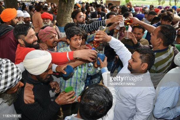 Indian devotees distribute liquor after giving offerings at the shrine of Baba Rode Shah in the village of Bhoma Wadala some 30 kms from Amritsar on...
