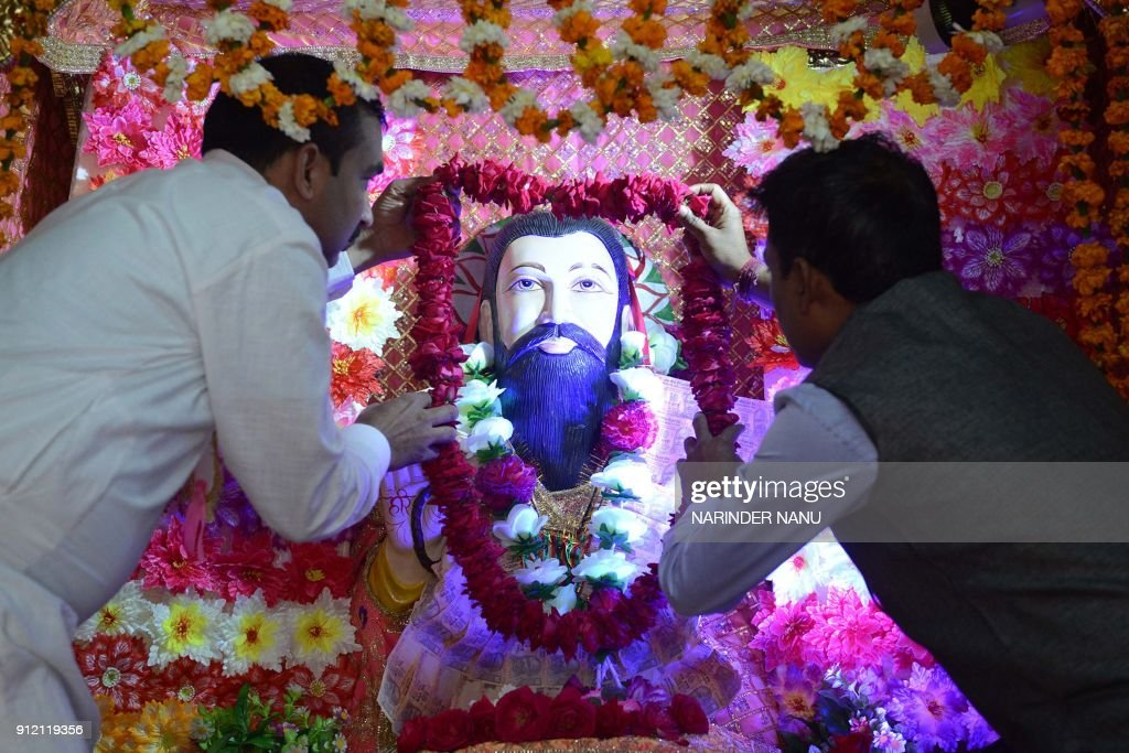 Indian devotees garlands an idol of Guru Ravidas on the eve of his 641th Birth Anniversary at a temple in Amritsar on January 30 2018 Guru Ravidas...