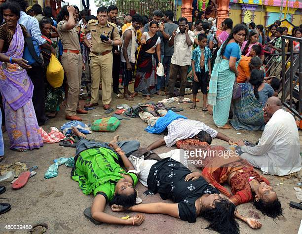 Indian devotees gather near the bodies of those killed after a stampede at a religious festival in Godavari in the Rajahmundry district some 200 kms...