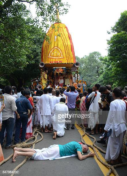 Indian devotees lies on a road as she touches a holy rope of the chariot during the Ulta Rath Yatra festival in Kolkata India on Thursday 14th July...