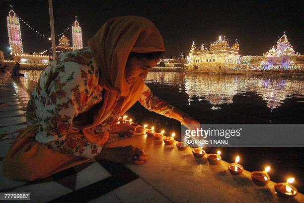 Indian devotees light candles in front of the illuminated Golden temple in Amritsar on the eve of Bandi Chhor Divas in Amritsar 08 November 2007...