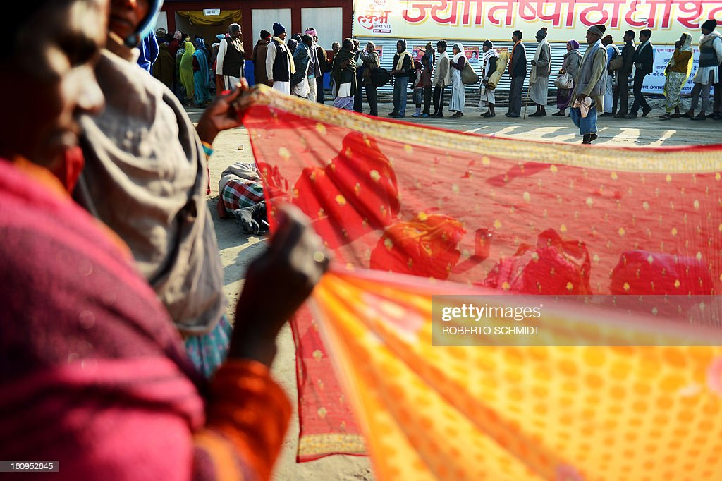 Indian devotees line up to receive a free meal near women drying saris at the entrance of one of hundreds of camps set up by different Hindu religious factions during the Maha Kumbh Mela festival in Allahabad on February 8, 2013. The Kumbh Mela in the town of Allahabad will see up to 100 million worshippers gather over 55 days to take a ritual bath in the holy waters, believed to cleanse sins and bestow blessings.