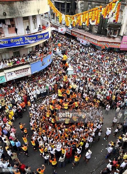 Indian devotees of Hindu God Lord Krishna gather to watch young men attempting to make a seventier human pyramid in the 'dahihandi' contest in Mumbai...
