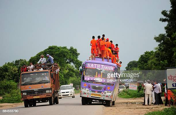Indian devotees of Lord Shiva kanwariya - travel on the roof of a bus on the way to collecting water from the Ganges river for their ritualistic walk...