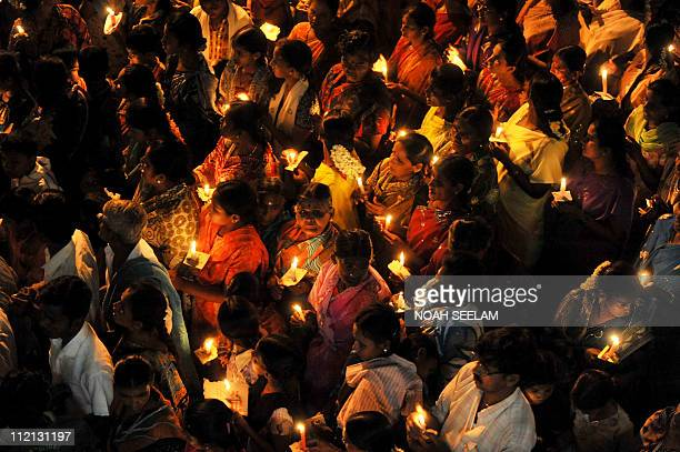 Indian devotees offer prayers during a candlelight vigil held for the speedy recovery of Satya Sai Baba outside the Prashanthi Nilayam at Puttaparthi...