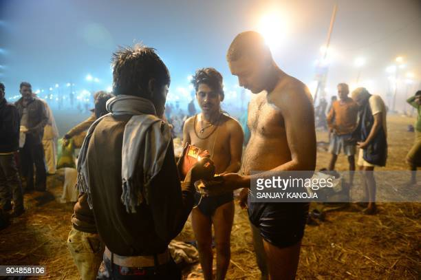 TOPSHOT Indian devotees perform rituals after taking a holy dip during the Makar Sankranti festival during the annual Magh Mela gathering at Sangam...