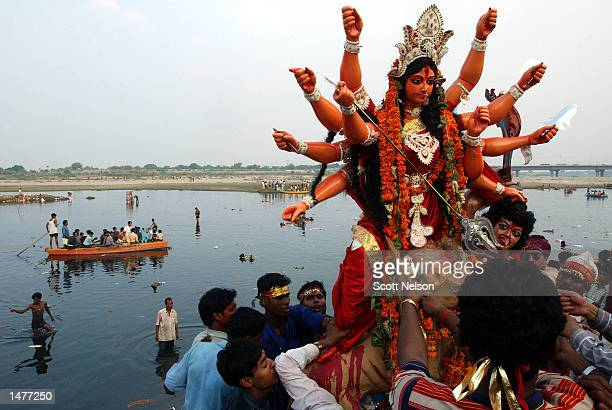 Indian devotees prepare to immerse a statue of the Hindu goddess Durga in the Yamuna river during a celebration marking the end of the Durga Puja...