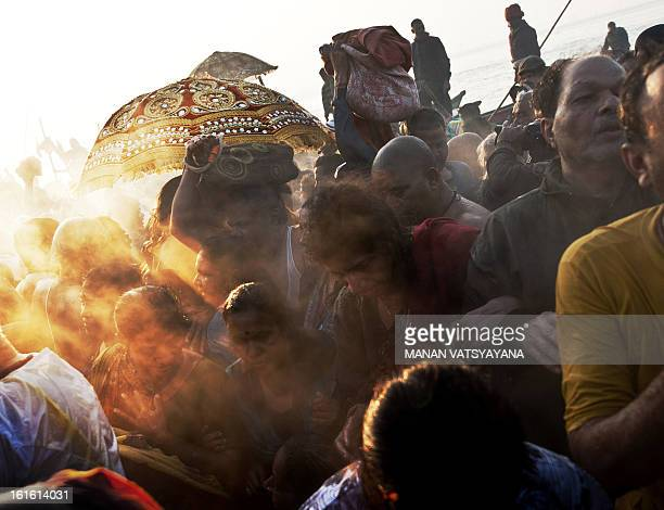 Indian devotees react as they see 'naga sadhus' holy men march towards the Sangam or confluence of the Yamuna Ganges and mythical Saraswati rivers at...