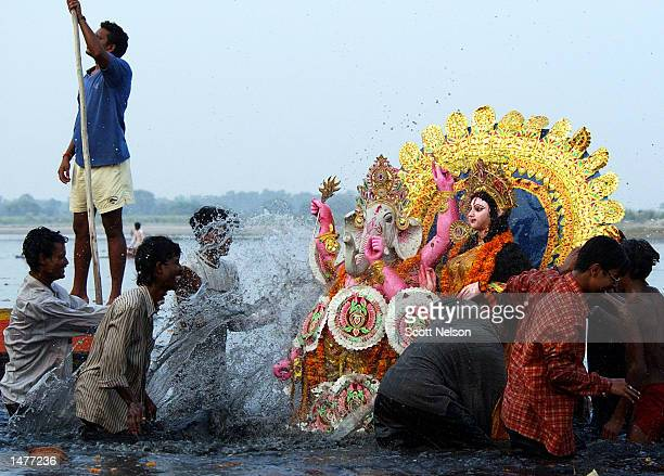 Indian devotees splash water on a statue of Hindu gods Ganesh and Durga as they immerse it in the Yamuna river during a celebration marking the end...