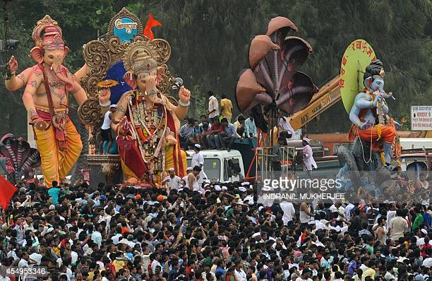 Indian devotees surround statues of the elephantheaded Hindu god Lord Ganesha before they are immersed in the Arabian sea at Chowpatty beach in...