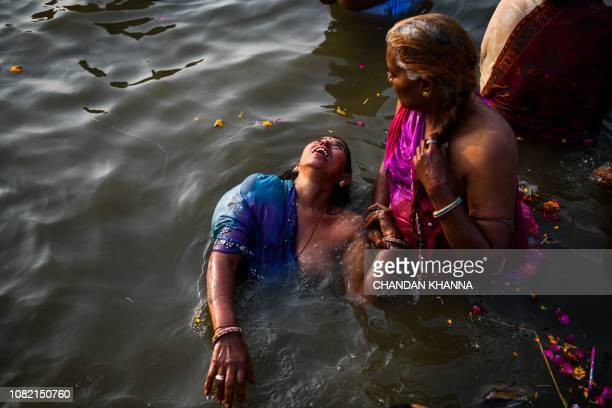 Indian devotees take a dip on the banks of the Triveni Sangam, the confluence of the Ganges, Yamuna and mythical Saraswati rivers, as people gather...