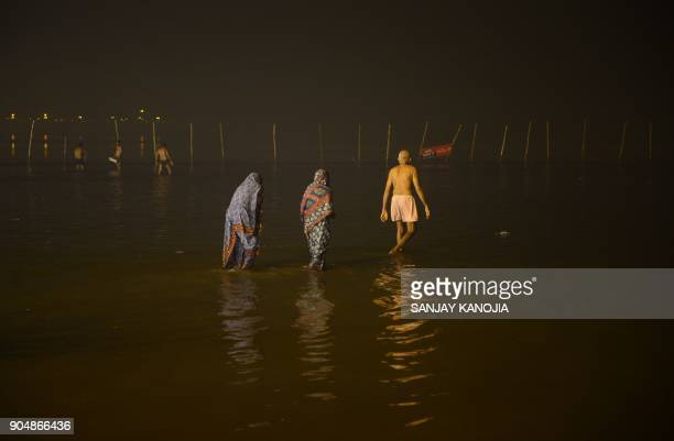 Indian devotees taking a holy dip on the occasion of Makar Sankranti festival during the annual 'Magh Mela' gathering at Sangam the confluence of the...