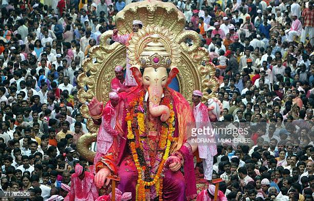 Indian devotees throng a major road as a huge idol of the elephant headed Hindu God Lord Ganesha is paraded through the streets of Mumbai 06...