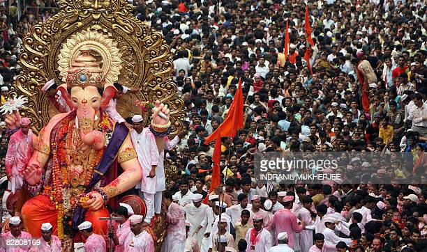 Indian devotees throng a major road as a huge idol of the elephant headed Hindu God Lord Ganesha is taken through the streets for immersion into the...