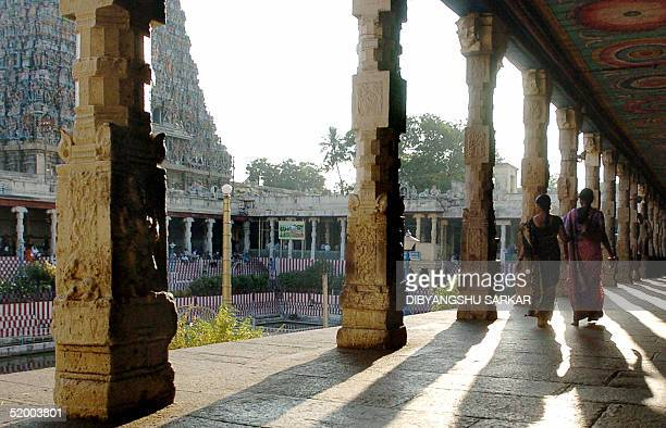 Indian devotees walk through a collonade at the Meenakshi Temple in Madurai some 475kms southwest of Madras 17 January 2005 The thirteenth century...