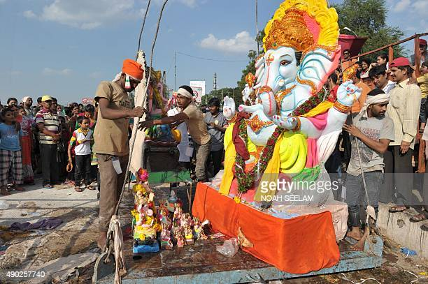 Indian devotees watch as workers prepare to immerse an idol of Hindu god Lord Ganesh in the Hussain Sagar Lake during the Ganesh Chaturthi festival...