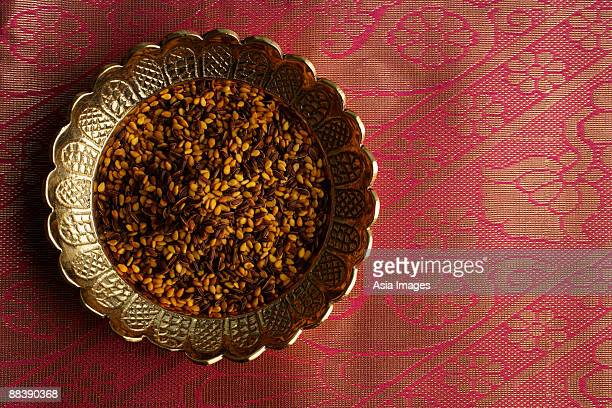 Indian digestive mukhwa seeds on brass dish on pink sari cloth