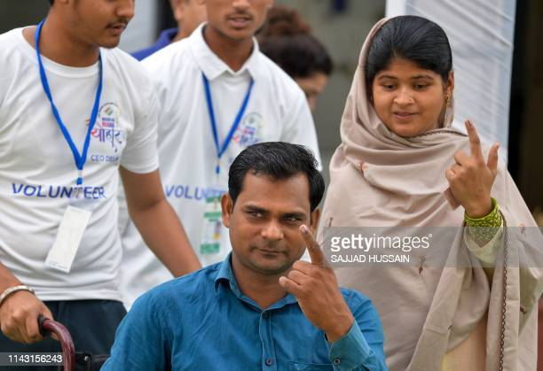 Indian disabled citizens show their inkmarked fingers after casting their vote at a polling station in New Delhi on May 12 2019 Fiftynine seats are...
