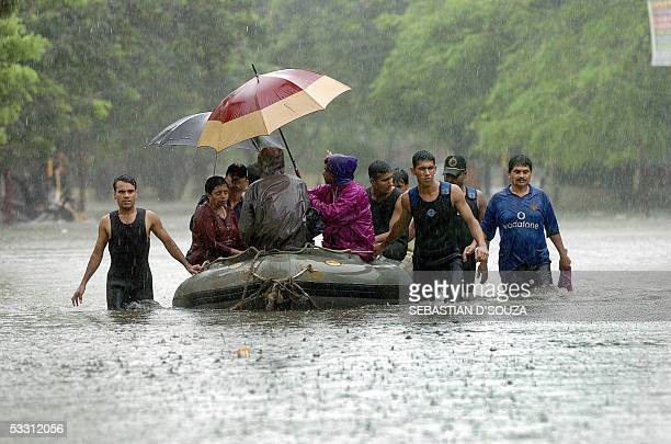 Indian divers and social workers carry out a rescue operation on a flooded street leading to the Air India residents quarters in Kalina in Mumbai 01...