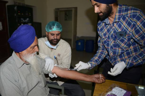 Indian doctor and specialists collecting DNA samples from Sardara Singh whose son Gurcharan Singh went missing in Iraq at the Forensic Medicine and...