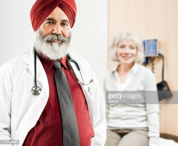 indian doctor posing with a patient in the background - sikh stock pictures, royalty-free photos & images