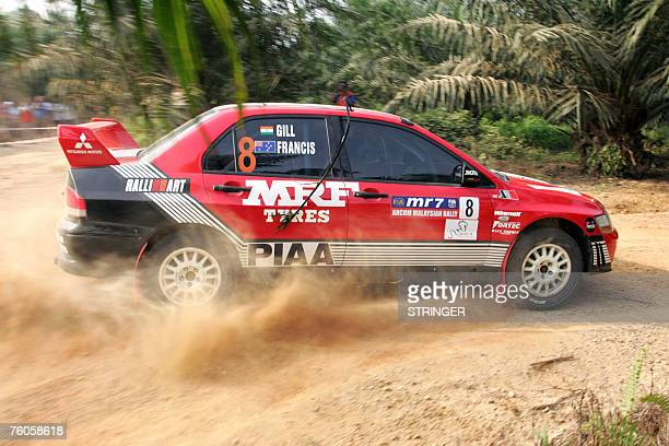 Indian driver Gaurav Gill and codriver Australian Karl Francis of MRF Tyres Rally Team slide sideways while kicking up dirt in their Mitsubishi...
