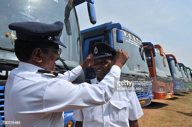 Indian drivers of The Andhra Pradesh State Road Transport Corporation adjust their hats as they stand in front of the newly equipped compressed...