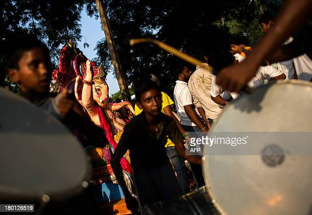 Indian drummers dance in the street near a Ganesh idol on the first day of the Ganesh Chaturthi festival in New Delhi on September 9 2013 The Hindu...