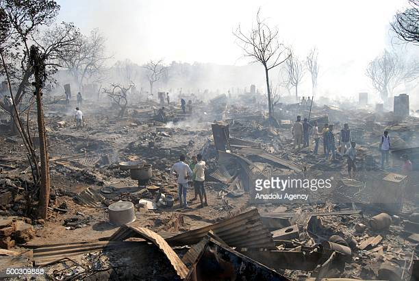 Indian dwellers collect their belongings from the charred remains following a fire at a slum in the east of Kandivali, an area in the north of Mumbai...
