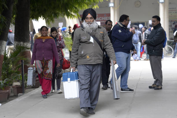 Indian election officials carry Electronic Voting Machines at a distribution centre in Jalandhar on February 3 2017 State Assembly elections are...
