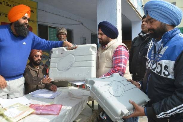 Indian election officials carry electronic voting machines from a distribution centre in Amritsar on February 3 2017 State Assembly elections are...