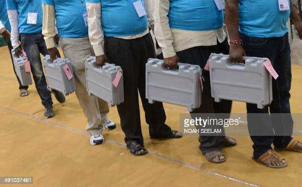 Indian election officials carry sealed Electronic Voting Machine at a counting centre in Hyderabad on May 16 2014 Hindu nationalist Narendra Modi...
