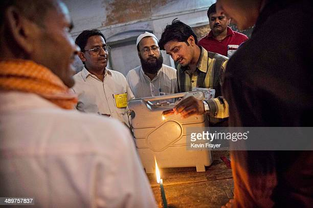 Indian election workers use a candle and hot wax to seal an electronic voting machine after the final polls closed at a polling station on May 12...