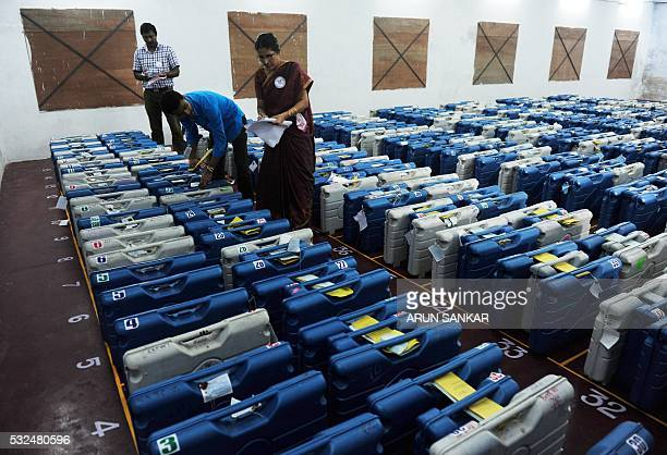Indian electoral counting officials verify Electronic Voting Machines in a strong room at a counting center in Chennai on May 19 2016 Votecounting is...