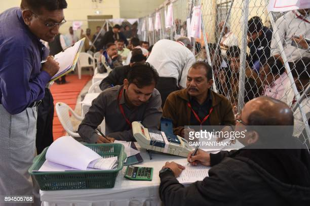 Indian electoral officials look at an electronic voting machine at the LD Engineering College campus in Ahmedabad on December 18 2017 / AFP PHOTO /...