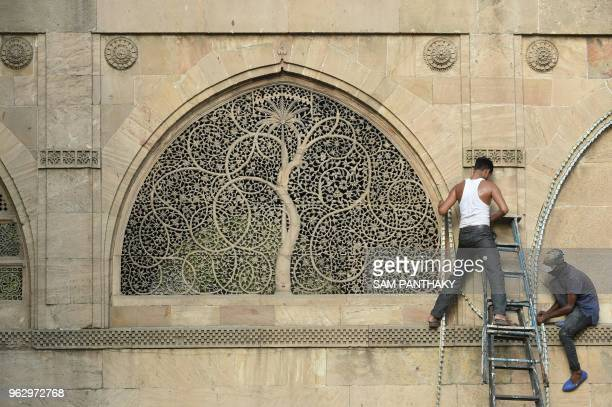 Indian electricians put lighting at the stone latticework depicting the 'Tree of Life' at the ancient Siddi Saiyed mosque during the holy Month of...