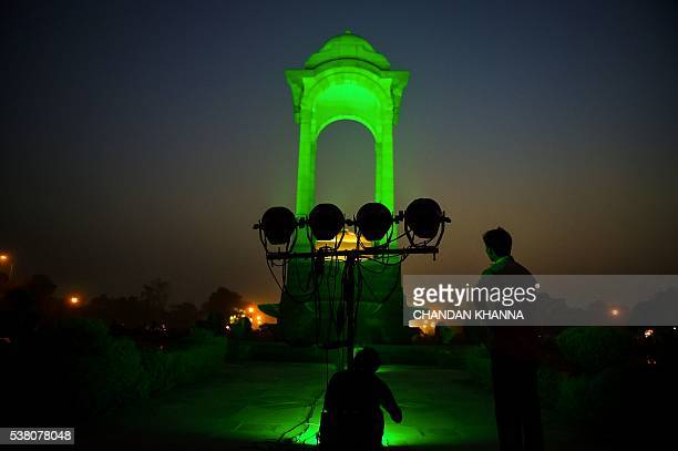 Indian Electricians Work At The Empty Canopy Structure Near India Gate As It Is Lit Green