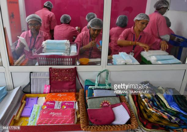Indian employees at the Myna Mahila Foundation prepare sanitary pads at their office in Mumbai on April 10 2018 An Indian charity championing...