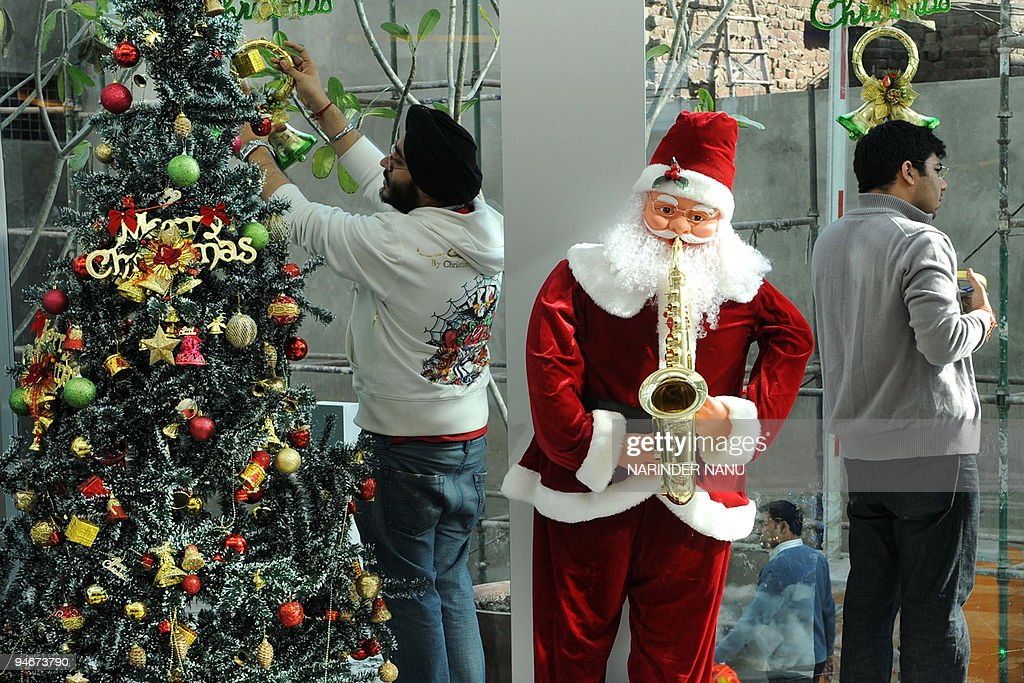 indian employees decorate a model of santa claus and a christmas tree at celebration mall in
