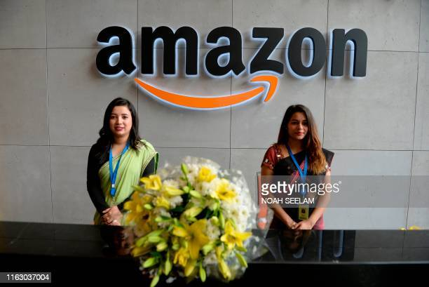 Indian employees stand at the reception desk of Amazon's newly inaugurated largest campus building in Hyderabad on August 21, 2019.